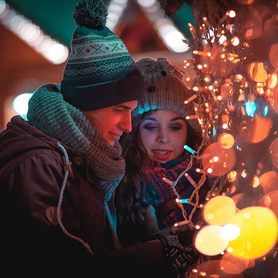 Happy couple in warm clothes enjoying colorul Christmas market, bokeh lights background