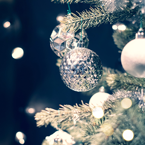Closeup of silver bauble hanging from a decorated Christmas tree