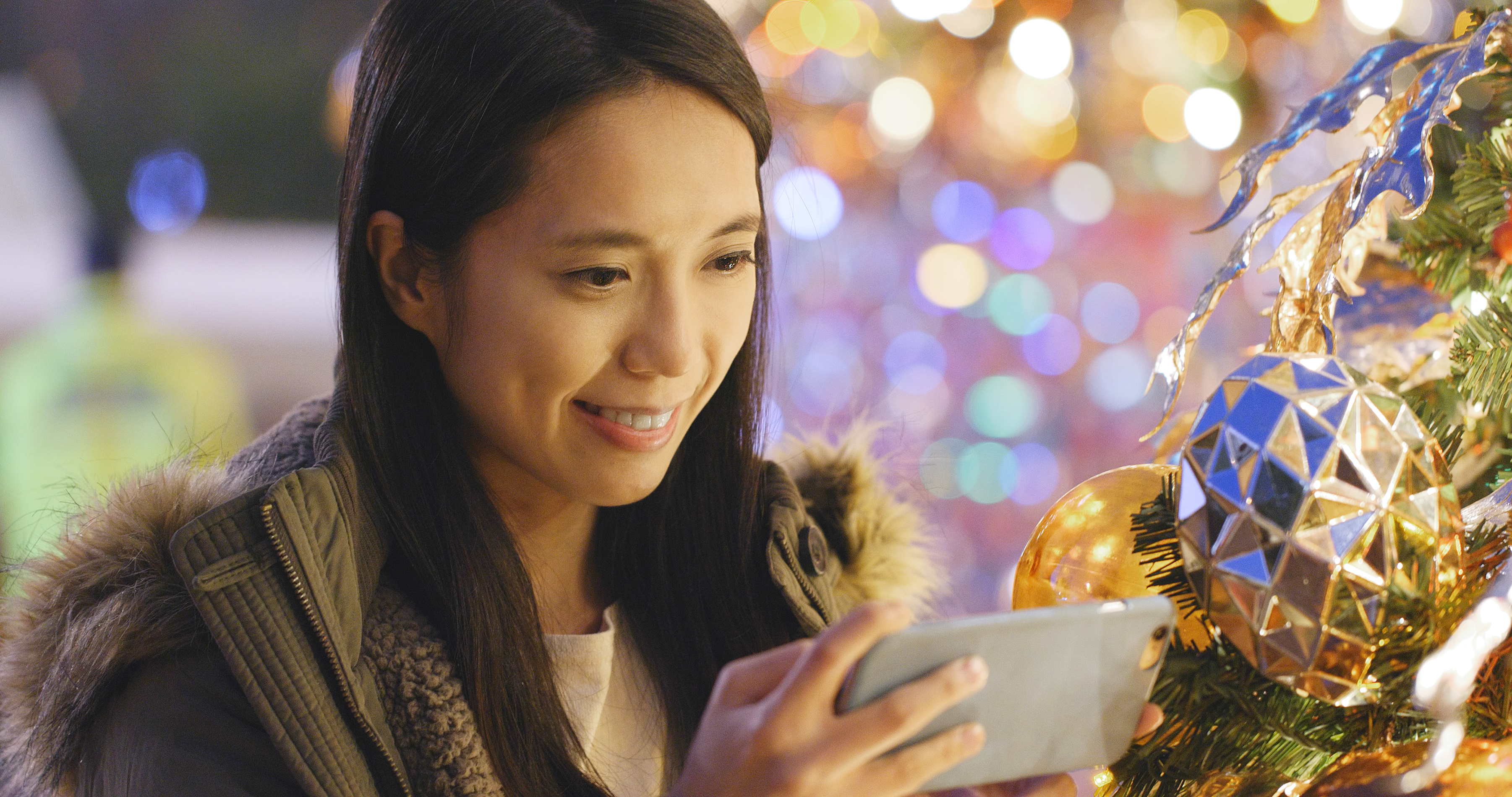 Woman taking photo on cellphone with Christmas tree decoration