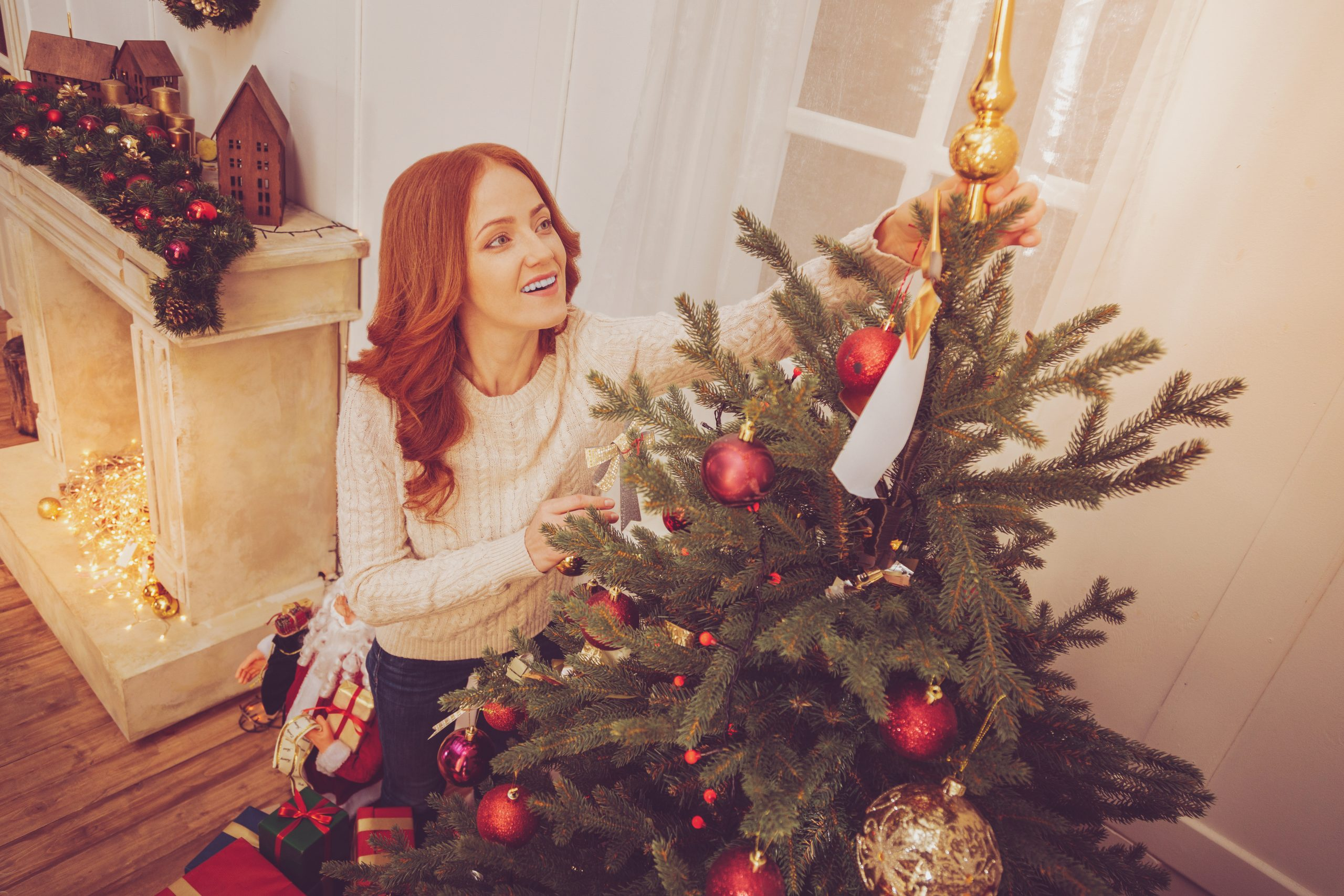 Last fine detail. Beautiful ginger-haired young woman standing near Christmas tree and putting a topper on it while smiling happily