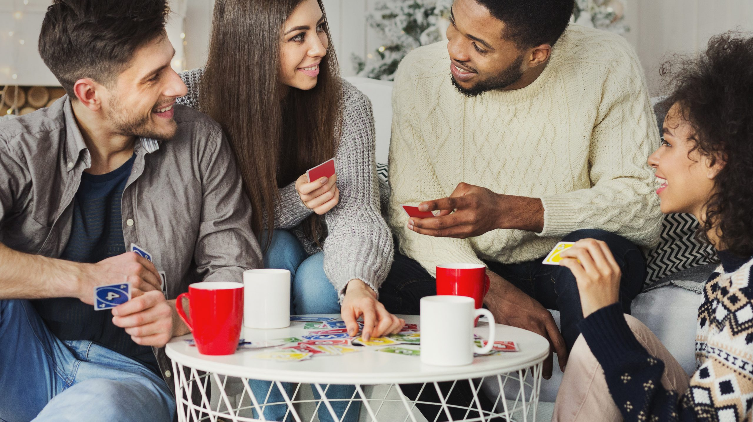 Multiracial friends having fun and playing game of cards UNO against christmas tree