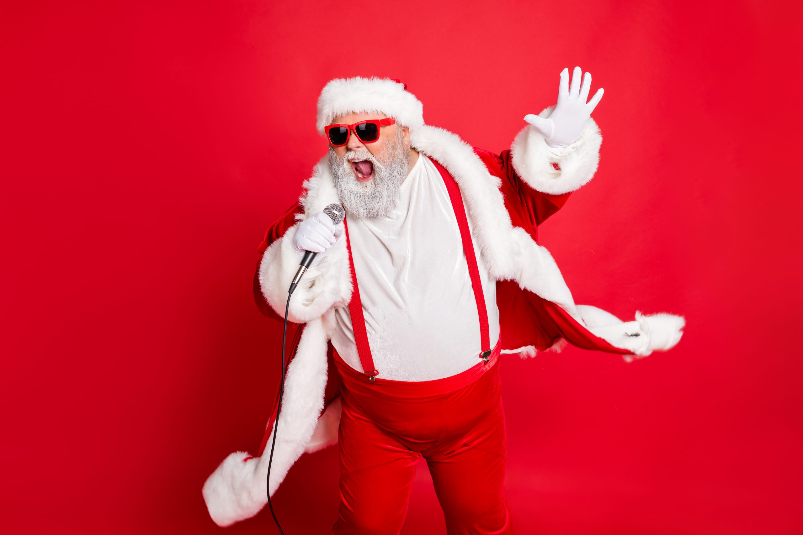 Portrait of cool funny fat overweight santa claus with big belly sing song on christmas party wear style stylish trendy eyeglasses eyewear, hat isolated over red background