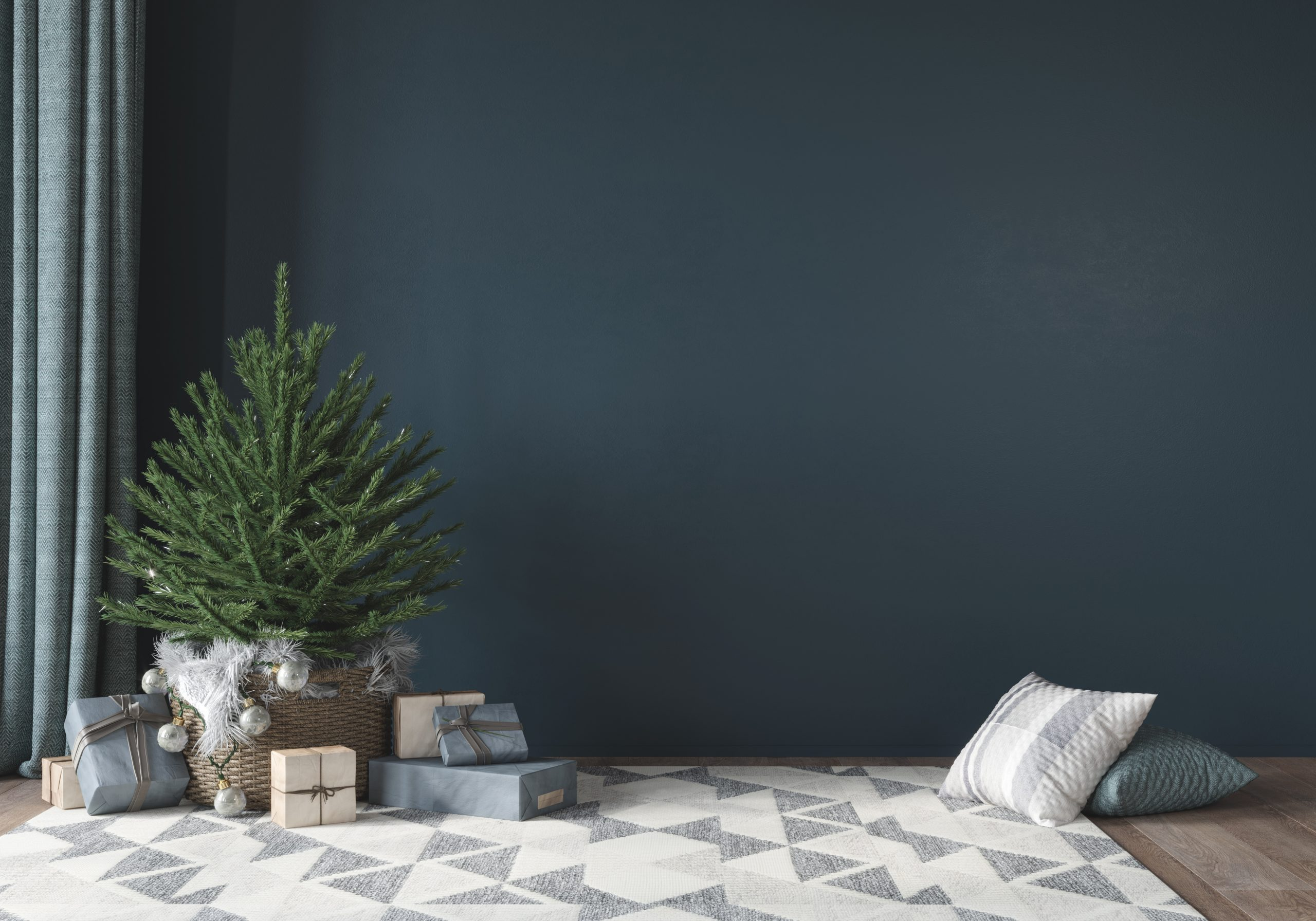 Festive interior with cute little christmas tree in basket, gifts and rug with geometric pattern on blue wall background